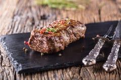 Μπριζόλα βόειου κρέατος Ψημένη μπριζόλα βόειου κρέατος με το αλατισμένο θυμάρι πιπεριών στον αγροτικό ξύλινο πίνακα Στοκ φωτογραφία με δικαίωμα ελεύθερης χρήσης