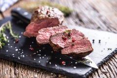 Μπριζόλα βόειου κρέατος Ψημένη μπριζόλα βόειου κρέατος με το αλατισμένο θυμάρι πιπεριών στον αγροτικό ξύλινο πίνακα Στοκ Φωτογραφία