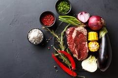 Μπριζόλα και λαχανικά ματιών πλευρών στο πιάτο στο μαύρο υπόβαθρο Στοκ εικόνες με δικαίωμα ελεύθερης χρήσης