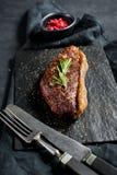 Μπριζόλα κεκλιμένων ραμπών βόειου κρέατος με το δεντρολίβανο Μαύρο υπόβαθρο, τοπ άποψη στοκ εικόνες