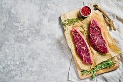 Μπριζόλα κεκλιμένων ραμπών βόειου κρέατος σε έναν ξύλινο τεμαχίζοντας πίνακα με το δεντρολίβανο και το ρόδινο πιπέρι Γκρίζο υπόβα στοκ εικόνες