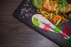 Μπριζόλα σολομών με τα πράσινα λεμονιών και σάλτσα στην πέτρα με το άλας στοκ φωτογραφία