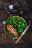 Μπριζόλα στη σχάρα κόκκαλων, τη σαλάτα του arugula και την ντομάτα κερασιών Στοκ εικόνες με δικαίωμα ελεύθερης χρήσης