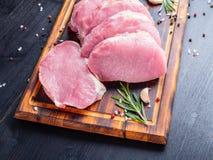 Μπριζόλα χοιρινού κρέατος, ακατέργαστη λωρίδα ανθρακικού άλατος στο σκοτεινό υπόβαθρο, κρέας με το ρ στοκ εικόνα με δικαίωμα ελεύθερης χρήσης