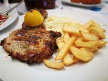 Μπριζόλα χοιρινού κρέατος με τις τηγανιτές πατάτες και το λεμόνι Στοκ Εικόνα