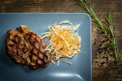 Μπριζόλα χοιρινού κρέατος στο πιάτο, τοπ άποψη Στοκ Εικόνες