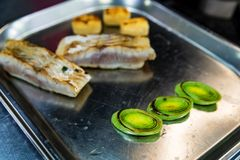 Μπριζόλα ψαριών με τα λαχανικά στο δίσκο μετάλλων στοκ εικόνα