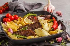Μπριζόλες βόειου κρέατος που ψήνονται στη σχάρα με τις ψημένα πατάτες και τα λαχανικά σε ένα τηγάνι Στοκ Εικόνες