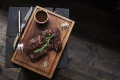 Μπριζόλα βόειου κρέατος Κομμάτι του ψημένου στη σχάρα BBQ βόειου κρέατος που μαρινάρεται στα καρυκεύματα Στοκ φωτογραφία με δικαίωμα ελεύθερης χρήσης