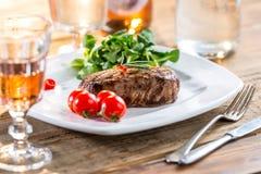 Μπριζόλα βόειου κρέατος juicy μπριζόλα βόειου κρέατος Γαστρονομική μπριζόλα με τα λαχανικά και το ποτήρι του ροδαλού κρασιού στον Στοκ Φωτογραφίες