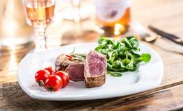 Μπριζόλα βόειου κρέατος juicy μπριζόλα βόειου κρέατος Γαστρονομική μπριζόλα με τα λαχανικά και το ποτήρι του ροδαλού κρασιού στον Στοκ Εικόνες