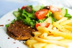 Μπριζόλα με τις τηγανιτές πατάτες και τη σαλάτα Στοκ Εικόνα