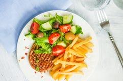 Μπριζόλα με τις τηγανιτές πατάτες και τη σαλάτα Στοκ Εικόνες