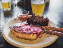Μπριζόλα με το κόκκινες κρεμμύδι, τη σάλτσα, το μαρούλι και την μπύρα Στοκ εικόνες με δικαίωμα ελεύθερης χρήσης
