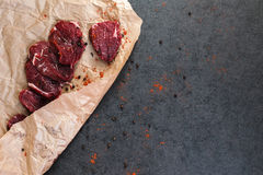 Μπριζόλα του βόειου κρέατος σε χαρτί και τα καρυκεύματα Στοκ Φωτογραφίες