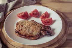 Μπριζόλα χοιρινού κρέατος και τεμαχισμένη ντομάτα σε ένα άσπρο πιάτο σε έναν ξύλινο στρογγυλό δίσκο Στοκ Φωτογραφίες