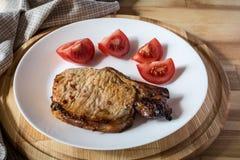 Μπριζόλα χοιρινού κρέατος και τεμαχισμένη ντομάτα Στοκ Φωτογραφία