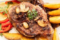Μπριζόλα χοιρινού κρέατος με τα μανιτάρια και τα τσιπ στοκ εικόνες με δικαίωμα ελεύθερης χρήσης