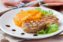 Μπριζόλα χοιρινού κρέατος που τηγανίζεται στη σχάρα με τις πολτοποιηίδες γλυκές πατάτες, νόστιμες Στοκ Εικόνες