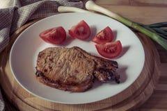 Μπριζόλα χοιρινού κρέατος, τεμαχισμένη ντομάτα σε ένα άσπρο πιάτο Στοκ φωτογραφία με δικαίωμα ελεύθερης χρήσης