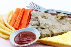 Μπριζόλα χοιρινού κρέατος, τηγανιτές πατάτες, κέτσαπ, ψωμί, άσπρο υπόβαθρο Στοκ Εικόνα