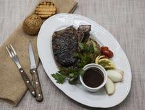 Μπριζόλα Ribeye από το μαρμάρινο κρέας βόειου κρέατος με τα λαχανικά και τη σάλτσα σχαρών Εξυπηρετημένος σε ένα πιάτο της μαύρης  Στοκ Φωτογραφία