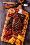 Μπριζόλες βόειου κρέατος με τις ψημένα στη σχάρα ντομάτες, τα μανιτάρια και το καλαμπόκι Στοκ εικόνα με δικαίωμα ελεύθερης χρήσης