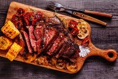 Μπριζόλες βόειου κρέατος με τις ψημένα στη σχάρα ντομάτες, τα μανιτάρια και το καλαμπόκι Στοκ Εικόνες