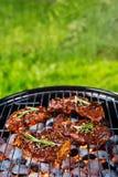Μπριζόλες βόειου κρέατος στη σχάρα σχαρών με τους φλογερούς άνθρακες Στοκ Φωτογραφίες