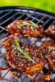 Μπριζόλες βόειου κρέατος στη σχάρα σχαρών με τους φλογερούς άνθρακες Στοκ Φωτογραφία