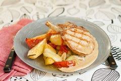 Μπριζόλες χοιρινού κρέατος με τις ψημένες στη σχάρα πατάτες και την πικάντικη σάλτσα Στοκ Εικόνα