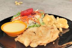 Μπριζόλες ψαριών και φυτική σαλάτα με τις τηγανιτές πατάτες Στοκ εικόνα με δικαίωμα ελεύθερης χρήσης