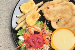 Μπριζόλες ψαριών και φυτική σαλάτα με τις τηγανιτές πατάτες Στοκ εικόνες με δικαίωμα ελεύθερης χρήσης