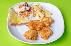 Μπριζόλες ψαριών, τηγανιτές πατάτες με τη σαλάτα λαχανικών Στοκ Εικόνες