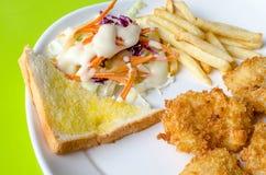 Μπριζόλες ψαριών, τηγανιτές πατάτες με τη σαλάτα λαχανικών Στοκ φωτογραφία με δικαίωμα ελεύθερης χρήσης