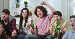 Μπροστά από τη χαρισματική κινηματογράφηση σε πρώτο πλάνο καμερών πολύ που προσέχει έναν αγώνα ποδοσφαίρου πίνοντας την μπύρα είν απόθεμα βίντεο