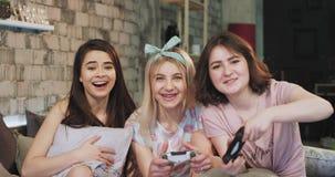 Μπροστά από το ελκυστικό ladie καμερών που παίζει στα τηλεοπτικά παιχνίδια ενός PlayStation στις πυτζάμες στην κρεβατοκάμαρα, πολ απόθεμα βίντεο