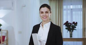 Μπροστά από το πορτρέτο καμερών μιας ελκυστικής επιχειρηματία σε ένα χαμόγελο κοστουμιών μεγάλο με τα άσπρα δόντια και το κράτημα απόθεμα βίντεο