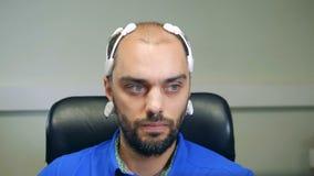 Μπροστινή άποψη ενός ατόμου που φορά μια κάσκα βιολογικού σήματος EEG απόθεμα βίντεο