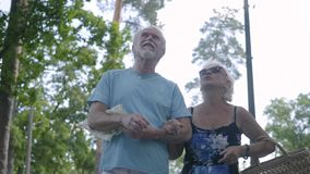 Μπροστινή άποψη ενός ευτυχούς ώριμου ζεύγους που περπατά στο πάρκο από κοινού Ανώτερη γυναίκα που κρατά την τσάντα, ο άνδρας που  απόθεμα βίντεο