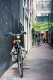 Μπροστινή άποψη ενός κλασικού αστικού ποδηλάτου με την πορτοκαλιές σέλα και την τσάντα Στοκ Εικόνες