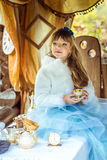 Μπροστινή άποψη ενός μικρού όμορφου κοριτσιού στο τοπίο της Alice στη χώρα των θαυμάτων που κρατά ένα φλυτζάνι του τσαγιού στον π Στοκ Φωτογραφία
