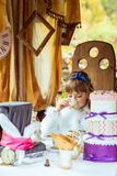 Μπροστινή άποψη ενός μικρού όμορφου κοριτσιού στο τοπίο της Alice στη χώρα των θαυμάτων που πίνει ένα τσάι στον πίνακα στο πάρκο Στοκ Εικόνες