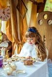 Μπροστινή άποψη ενός μικρού όμορφου κοριτσιού στο τοπίο της Alice στη χώρα των θαυμάτων που κρατά ένα φλυτζάνι του τσαγιού στον π Στοκ εικόνα με δικαίωμα ελεύθερης χρήσης