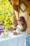 Μπροστινή άποψη ενός μικρού όμορφου κοριτσιού στο τοπίο της Alice στη χώρα των θαυμάτων που κρατά ένα φλυτζάνι του τσαγιού στον π Στοκ Εικόνες