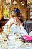 Μπροστινή άποψη ενός μικρού όμορφου κοριτσιού στο τοπίο της Alice στη χώρα των θαυμάτων που πίνει ένα τσάι στον πίνακα στο πάρκο Στοκ Φωτογραφία
