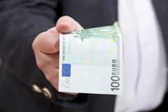 Μπροστινή άποψη 100 ευρο- τραπεζογραμμάτιο στο χέρι επιχειρηματιών Στοκ Εικόνες