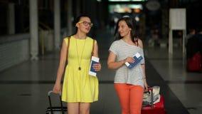 Μπροστινή άποψη ελκυστικού Brunettes με τις αποσκευές στον αερολιμένα Οι γελώντας θηλυκοί φίλοι έχουν ένα ταξίδι από κοινού Γυναί απόθεμα βίντεο