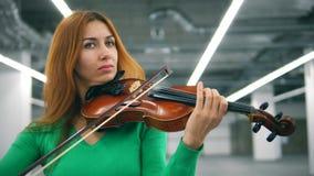 Μπροστινή άποψη μιας γυναίκας με την τρίχα χαλκού που παίζει το βιολί απόθεμα βίντεο