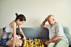 Μπροστινή άποψη σκακιού εγγονών και grandpa παίζοντας Στοκ φωτογραφία με δικαίωμα ελεύθερης χρήσης